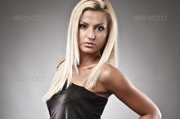 Full length portrait of a fashionable blond woman on gray background