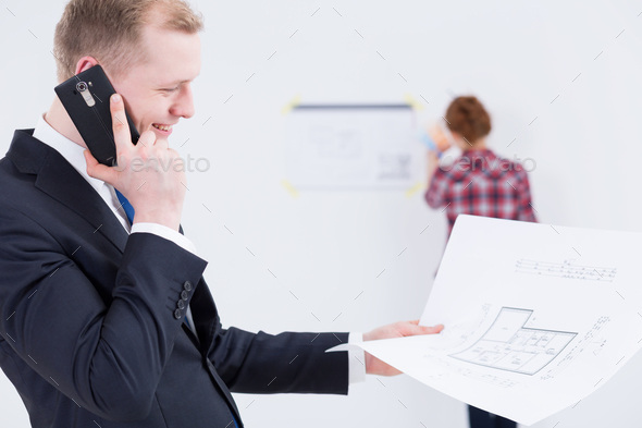 Man in suit talking on the phone with the architectural project in his hand