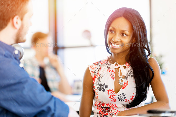 Portrait of beautiful smiling afro-american office worker sitting in office