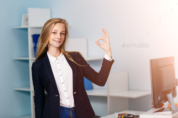 Young pretty business woman makes OK sign in blue office
