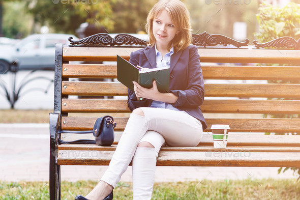 Woman sitting on the bench with diary picture