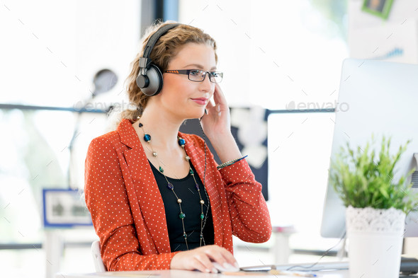 Young woman in casual clothes sitting in office in headphones