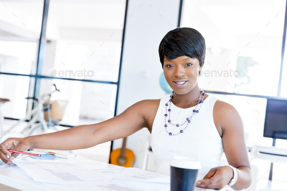 Young beautiful woman sitting at a desk in an office and working on blueprint