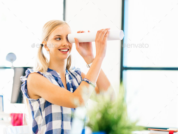 Young woman in casual clothes in an office with a paper tube