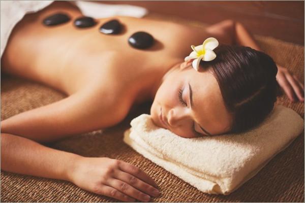 woman laying on bed and enjoying stone massage