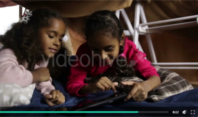 Two Little Sisters Playing with Tablet Pc at Home